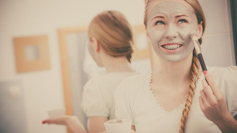 Woman applying with brush clay mud mask to her face. Skincare. Blonde woman in bathroom applying with brush gray clay mud mask to her face. Young lady taking royalty free stock photos