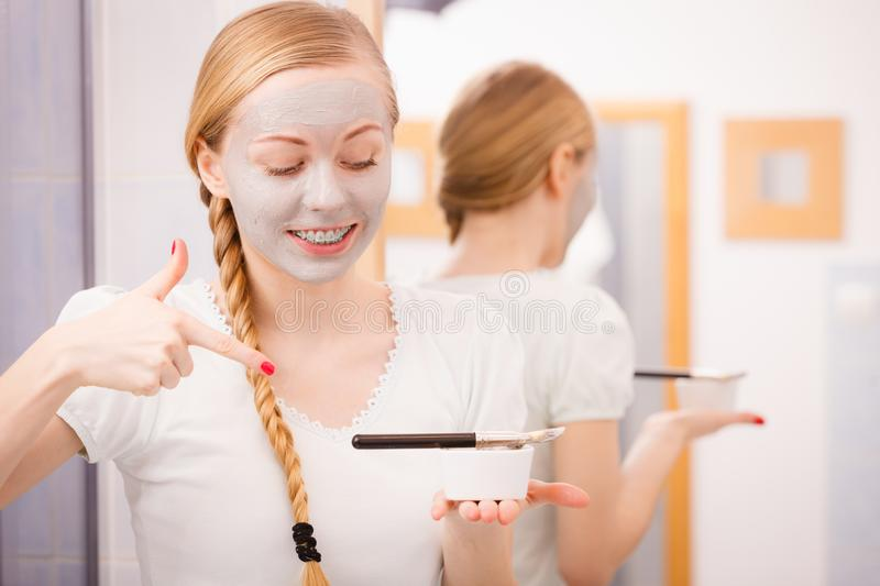 Woman applying with brush clay mud mask to her face. Skincare. Blonde smiling woman in bathroom gray clay mask on her face pointing with finger on bowl with mud stock photo