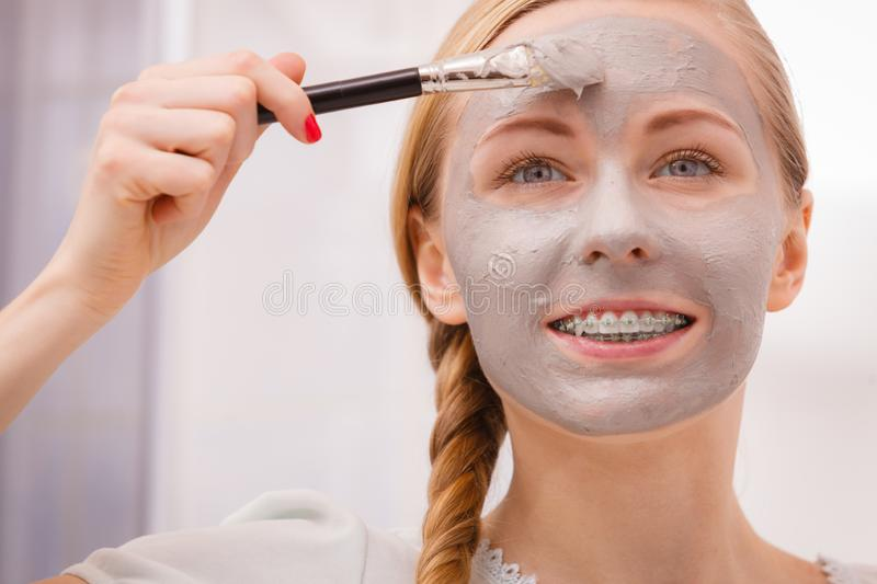 Woman applying with brush clay mud mask to her face. Skincare. Young woman applying with brush grey clay mud mask to her face. Female taking care of skin royalty free stock image
