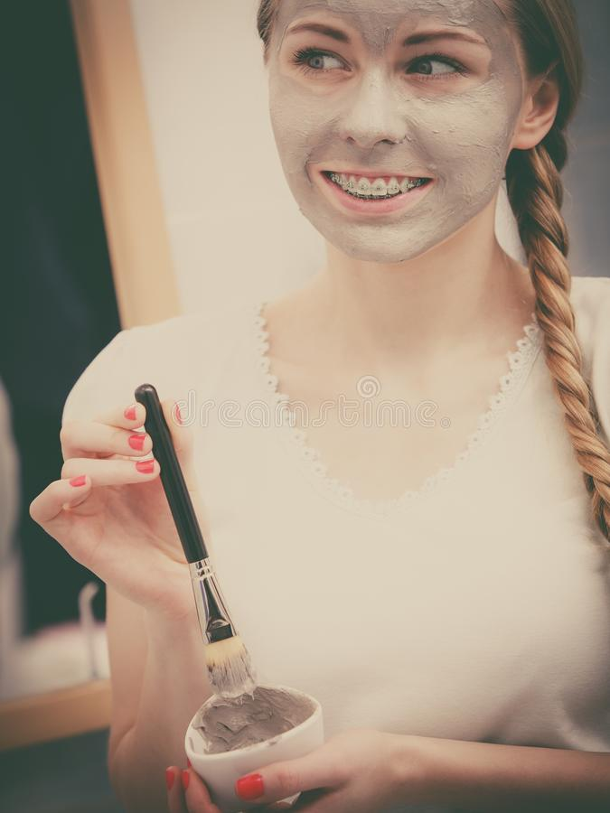 Woman applying with brush clay mud mask to her face. Skincare. Young woman applying with brush grey clay mud mask to her face. Female taking care of skin stock image