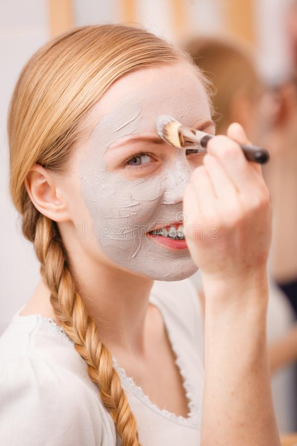 Woman applying with brush clay mud mask to her face. Skincare. Young woman applying with brush grey clay mud mask to her face. Female taking care of skin stock photography