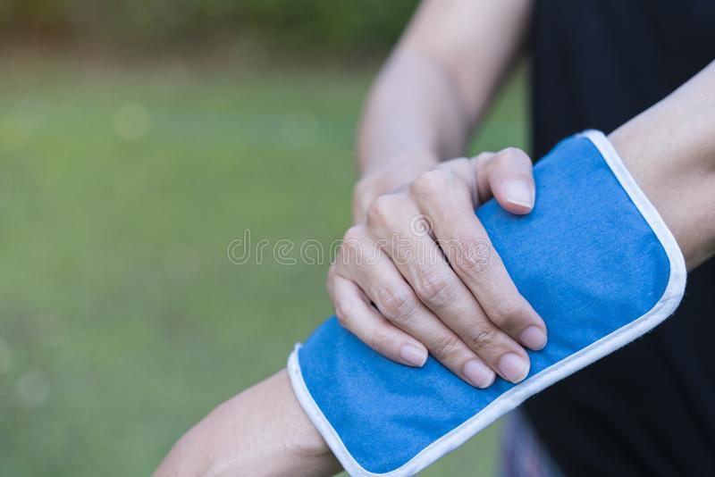 Woman applying cold pack on her arm. Close up stock photography