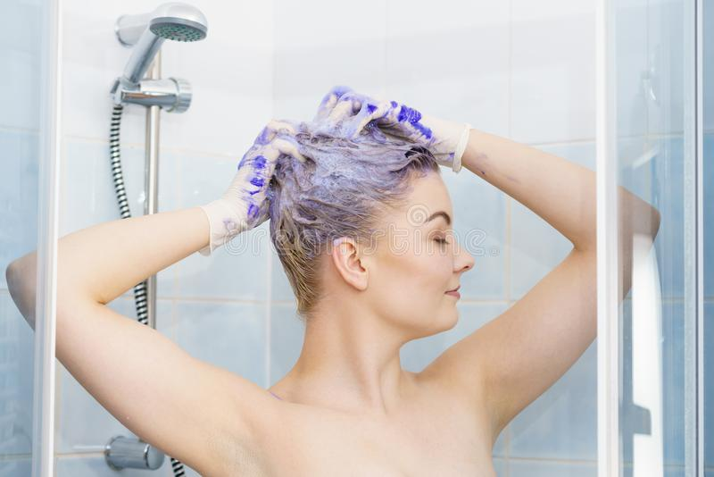 Woman applying toner shampoo on her hair. Woman applying coloring shampoo on her hair. Female having purple washing product. Toning blonde color at home royalty free stock photo