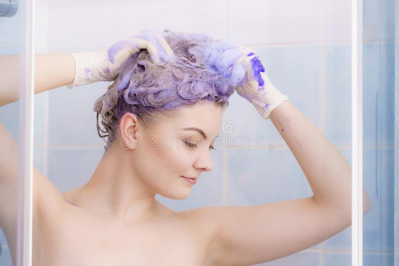 Woman applying toner shampoo on her hair royalty free stock images