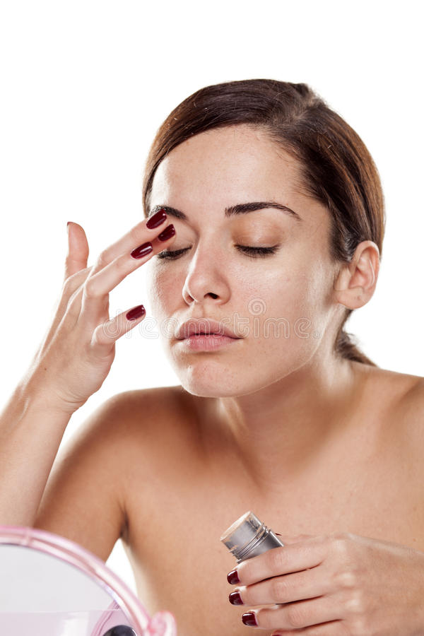 Woman applying concealer. Beautiful young woman applying concealer around her eyes royalty free stock images