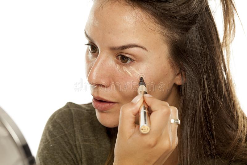 Woman applying concealer. Young woman applying concealer under her eyes on a white background royalty free stock photo
