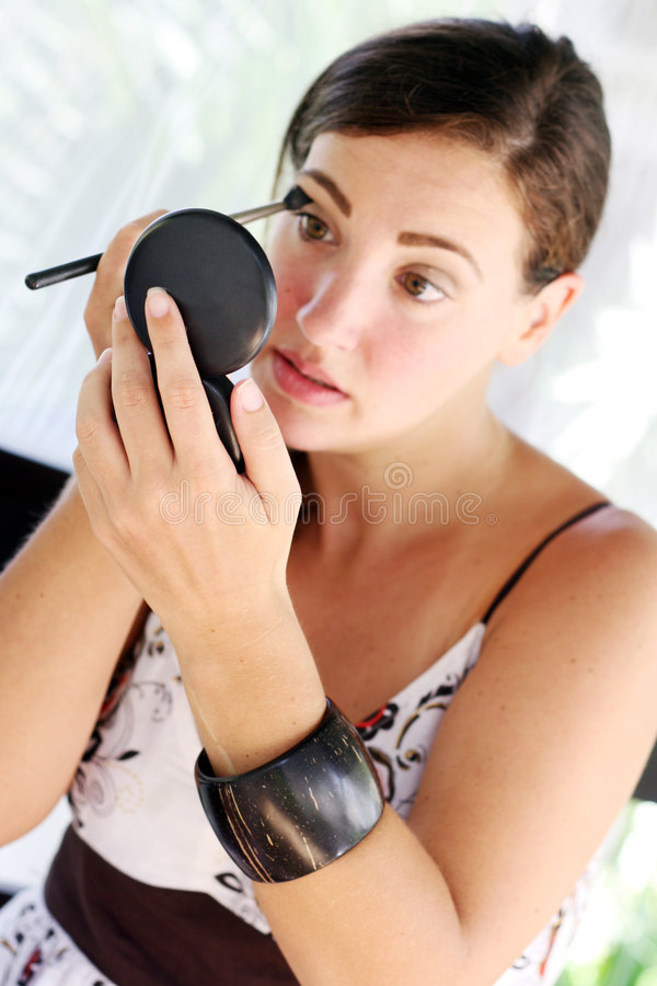 Woman applying cosmetics stock photo