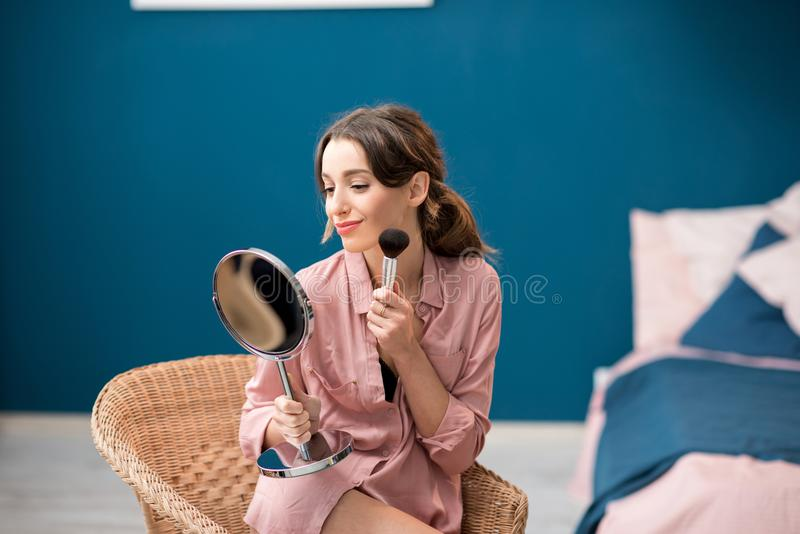 Woman applying cosmetics indoors royalty free stock photos