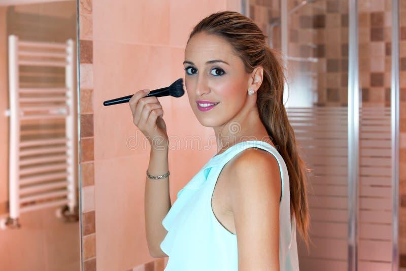 Woman applying cosmetics with makeup brush stock photography