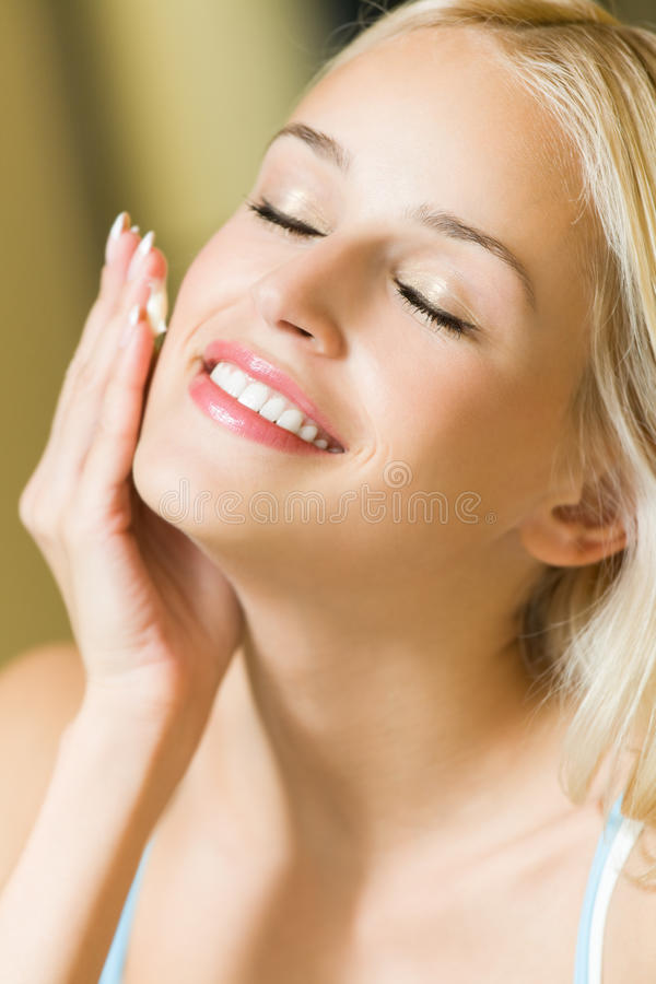 Woman applying cream. Smiling woman applying cream at home royalty free stock image