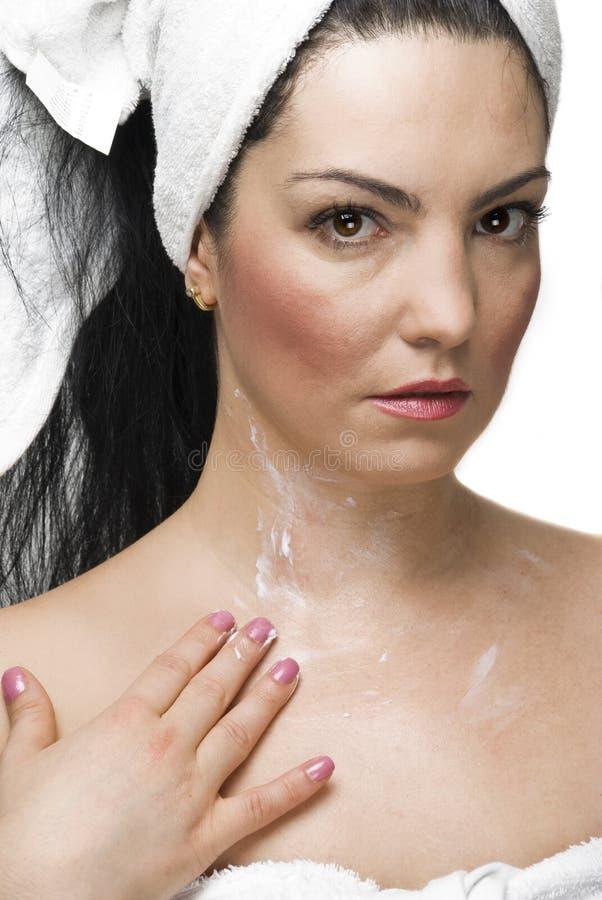 Woman applying cream on body stock photos