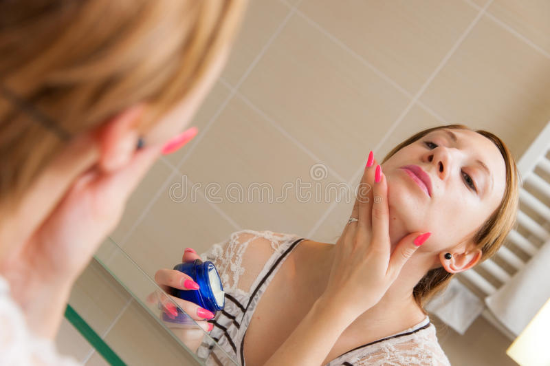 Woman Applying Cream on Face royalty free stock photography