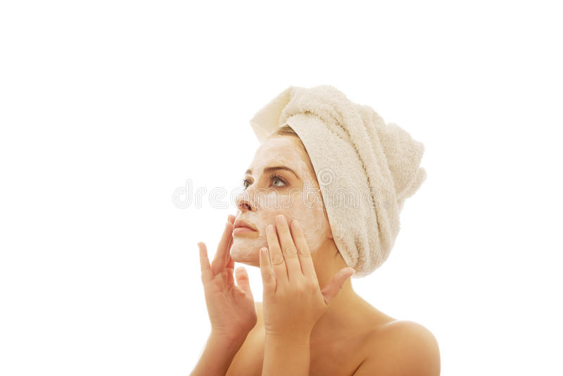 Woman applying a cream on her face royalty free stock image