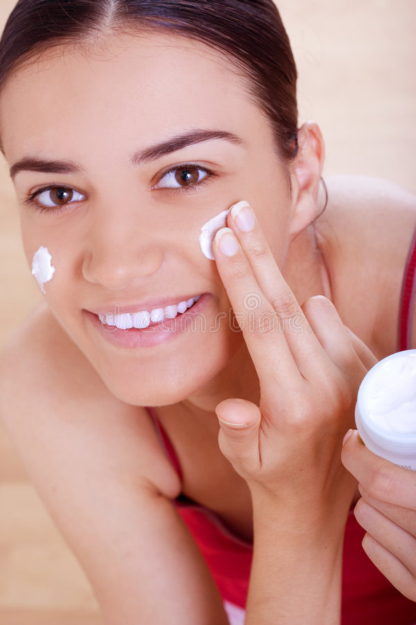 Woman applying cream on her face royalty free stock photos