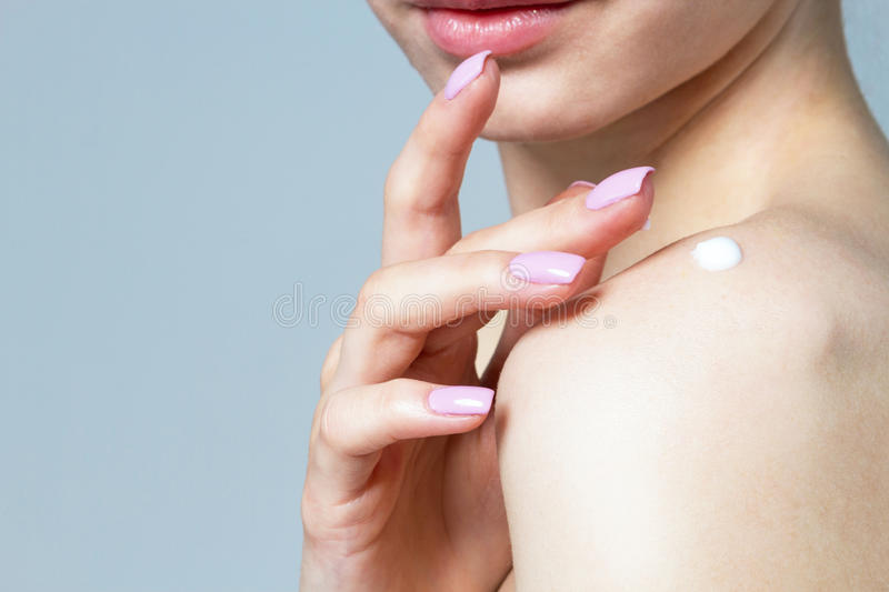 A woman is applying a cream on her shoulder. royalty free stock images