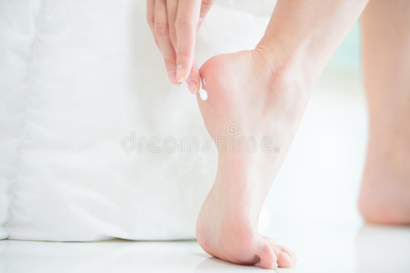 Woman applying cream onto heel stock images