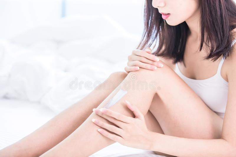 Woman applying cream onto leg. Woman applying cream onto her leg and shin at home stock images