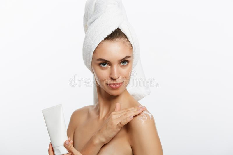 Woman applying cream on shoulder on a white background. stock photo