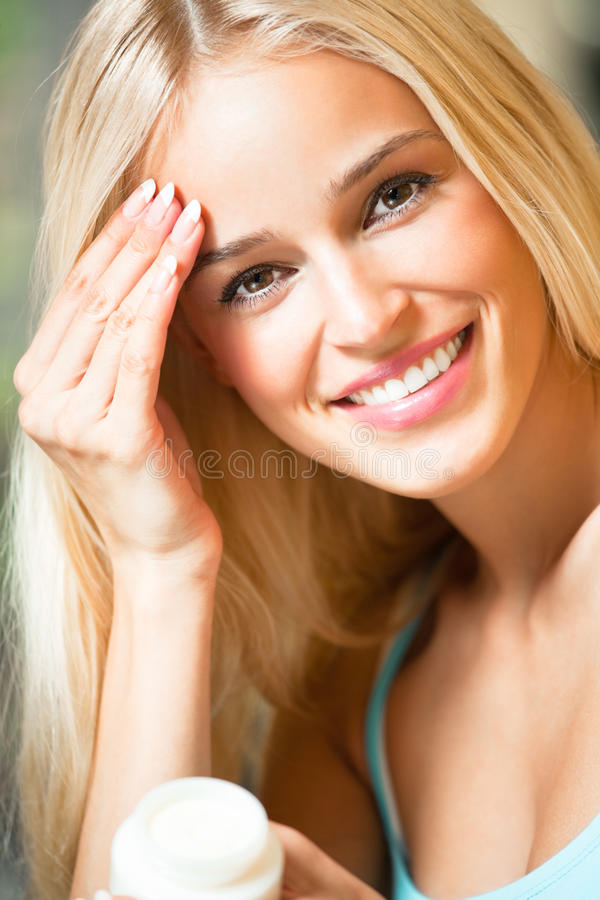 Woman applying creme stock photography