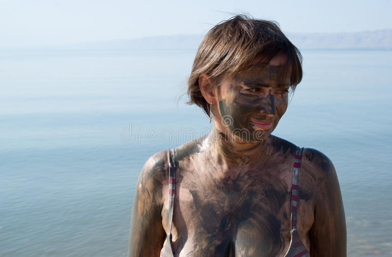 Woman applying Dead Sea mud body care treatment. Woman applying natural mineral mud, sourced from the Dead Sea stock photos
