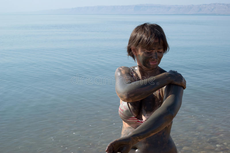 Woman applying Dead Sea mud body care treatment. Woman applying natural mineral mud, sourced from the Dead Sea stock photography