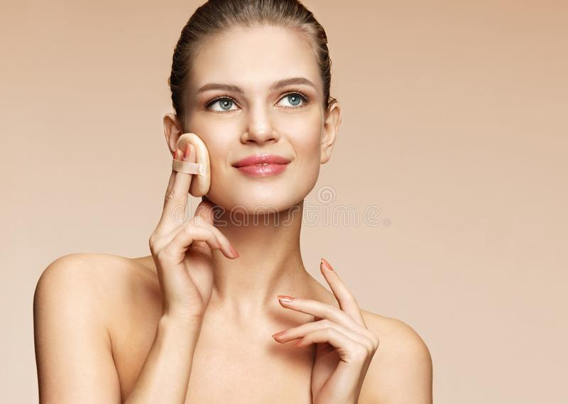 Woman applying dry powder using cosmetic cushion on her facial skin royalty free stock image
