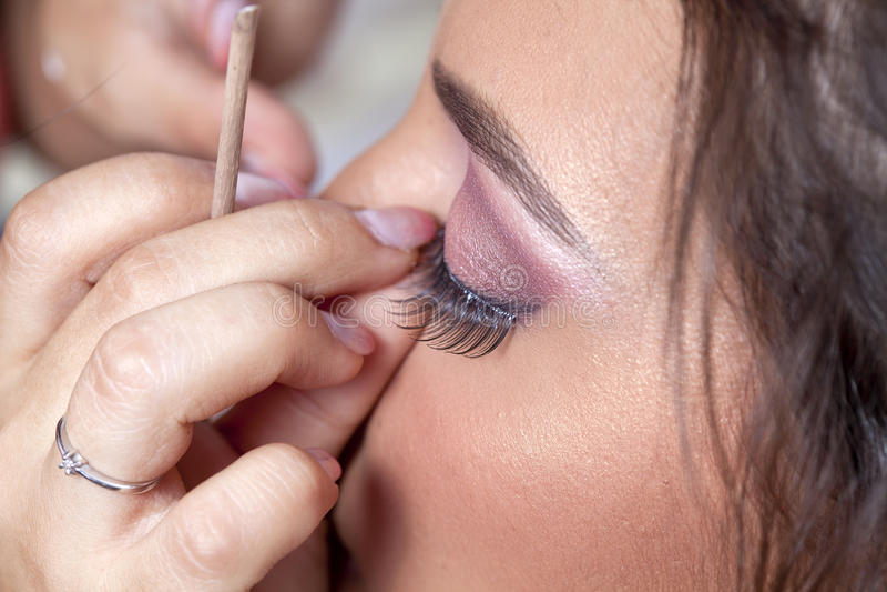 Woman applying eyelashes. Side portrait of young woman applying fake eyelashes royalty free stock photography
