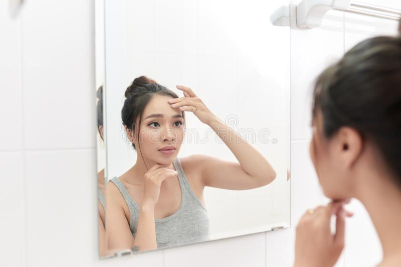 Woman applying face cream after daily shower. Making everyday morning routine in bathroom stock photos