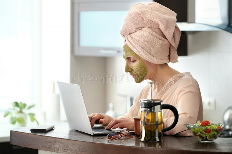 Woman applying facial clay mask. The young woman is working remotely. Concept of the workplace at home, working remotely. Creative royalty free stock photo