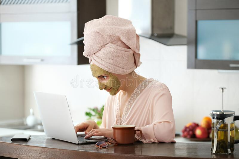 Woman applying facial clay mask. The young woman is working remotely. Concept of the workplace at home, working remotely. Creative stock photography