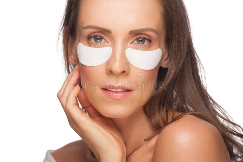Woman applying gel eye mask stock photography