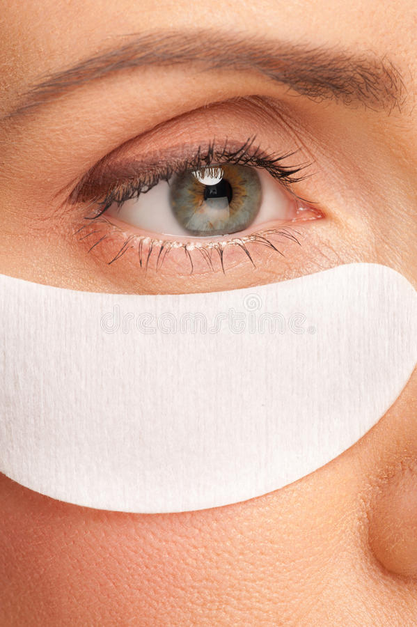 Woman applying gel eye mask stock image