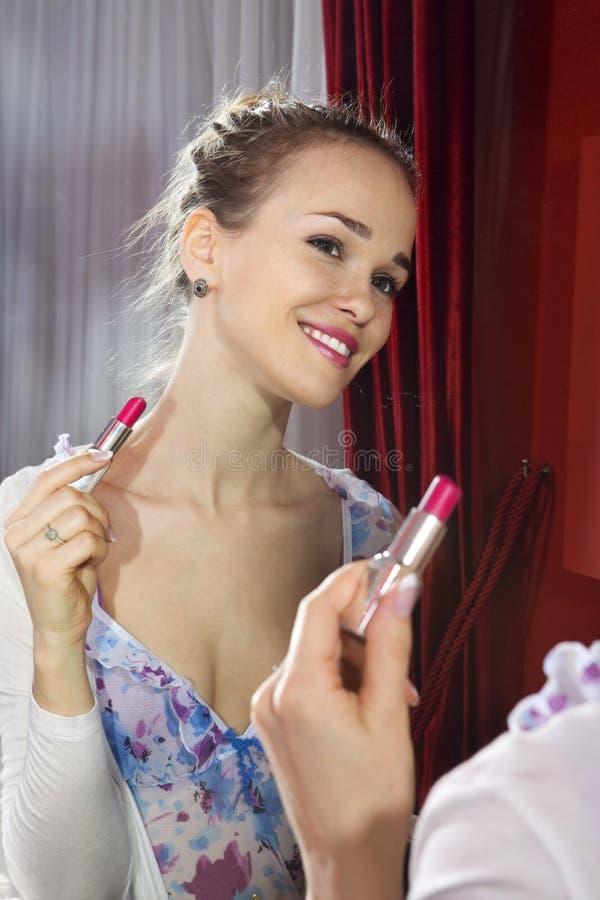 Woman applying her make-up stock image