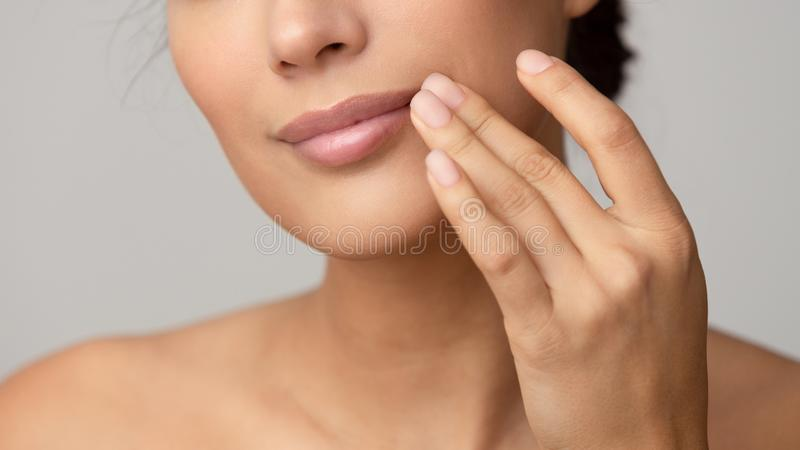 Woman applying lip balm over grey background. Woman applying lip balm over grey studio background stock image