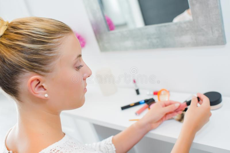 Woman applying lip gloss. Accessory stock photography