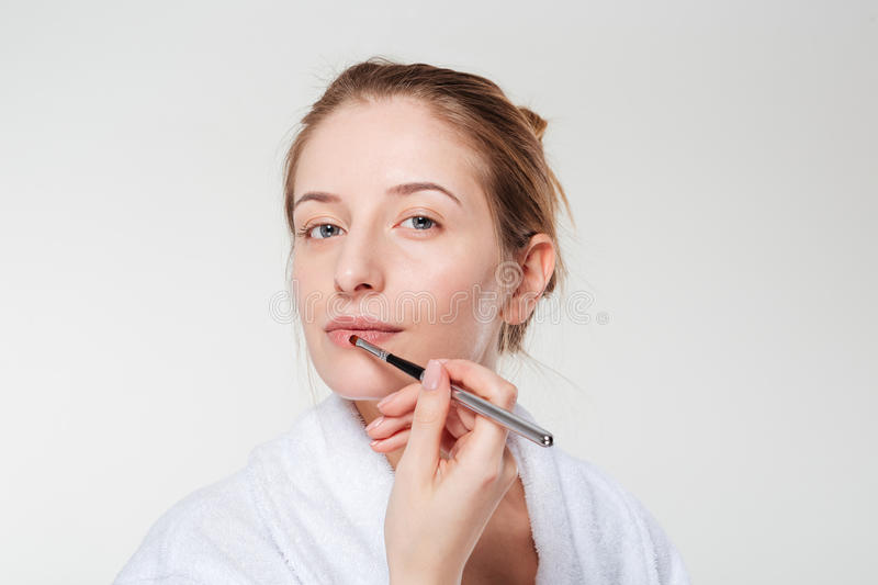 Woman applying lipstick with an applicator. Isolated on a white background stock image
