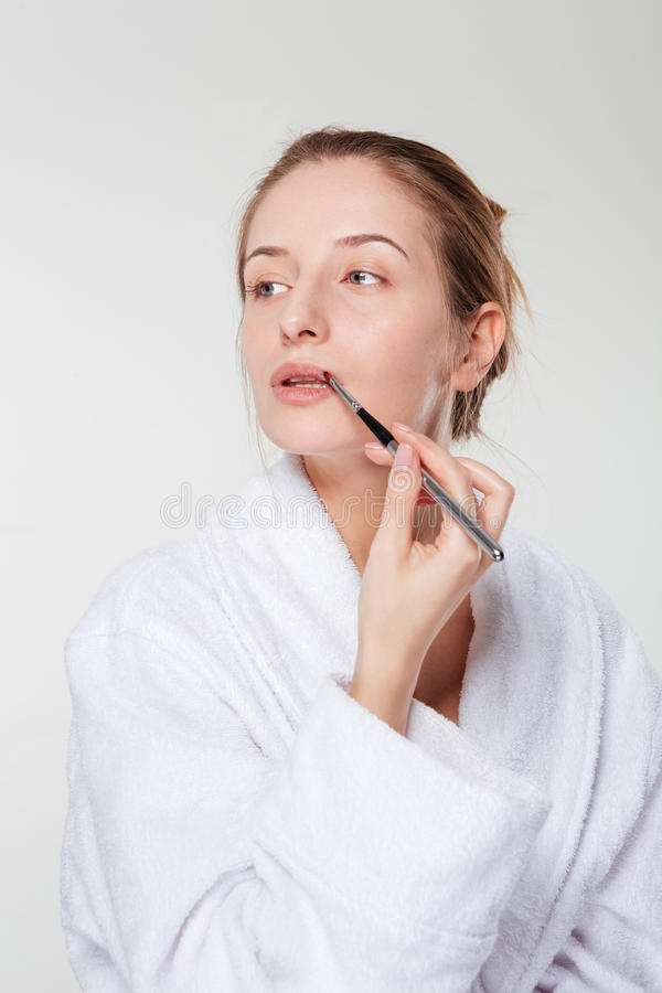 Woman applying lipstick with an applicator. Isolated on a white background and looking away royalty free stock images