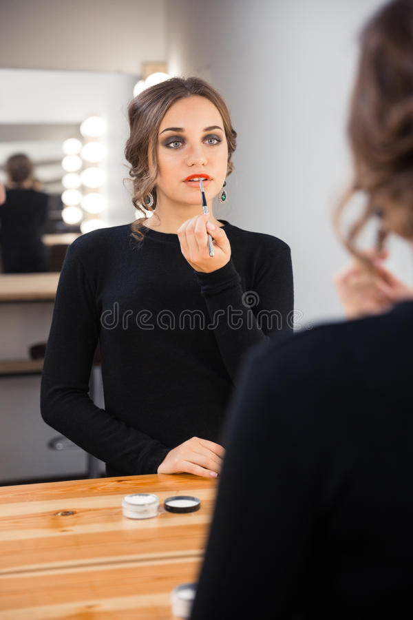 Woman applying lipstick on her lips. Portrait of a young woman applying lipstick on her lips stock images