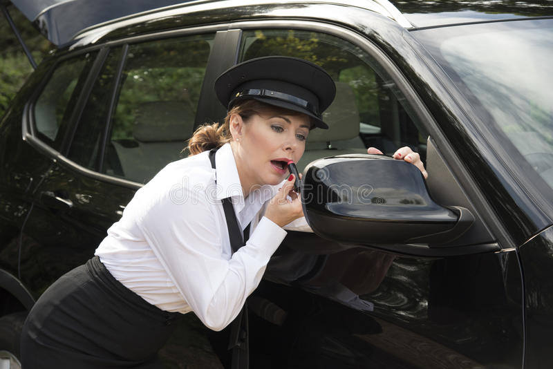 Woman applying lipstick looking in car wing mirror royalty free stock image