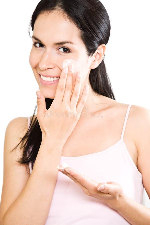 Woman applying lotion stock photography
