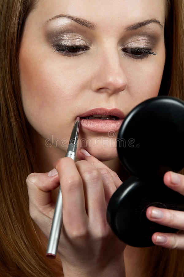 Woman applying make up stock photos