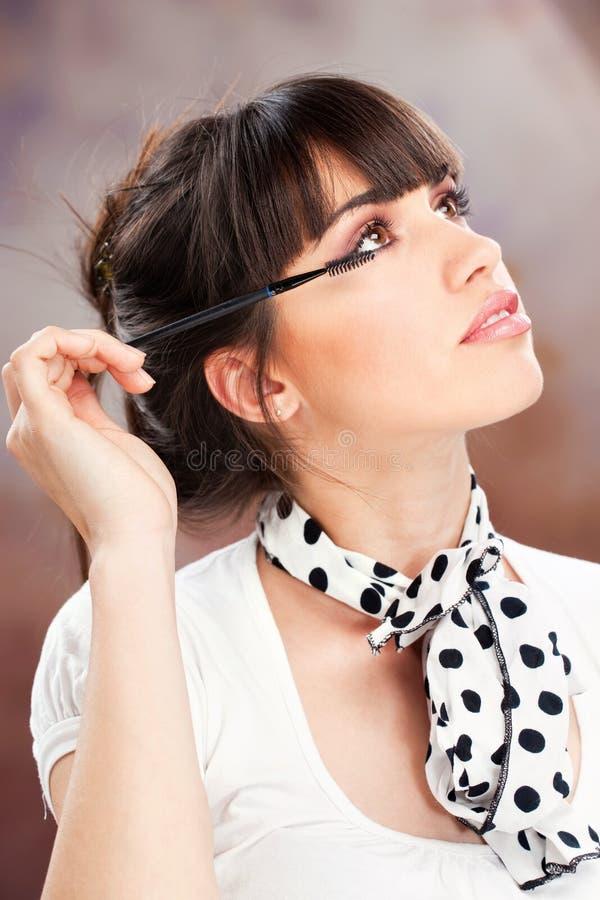Woman applying makeup on eyelash stock photography