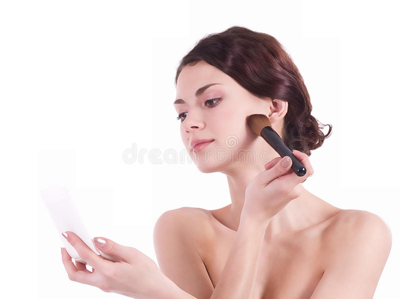 Woman applying makeup on face stock image