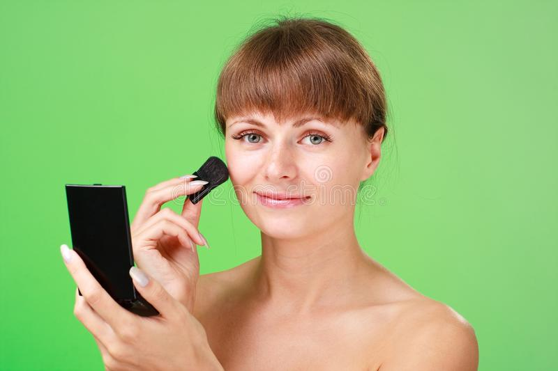 Download Woman Applying Makeup On A Green Background Stock Image - Image: 11780217