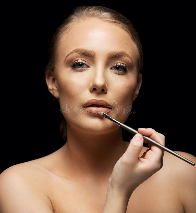 Woman Applying Makeup On Lips Royalty Free Stock Images
