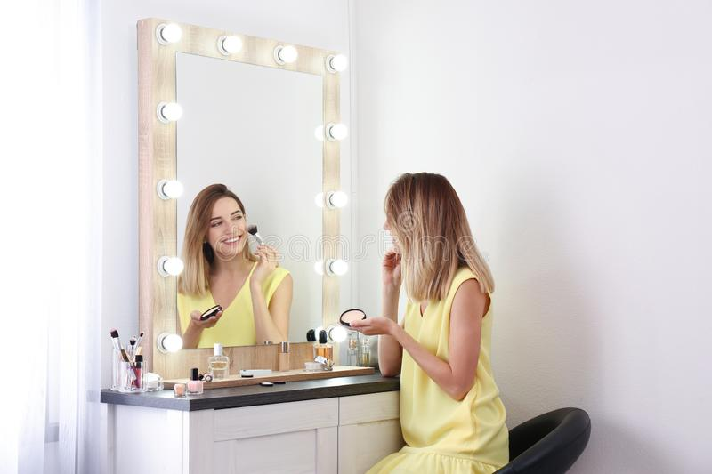 Woman applying makeup near mirror with light bulbs royalty free stock images