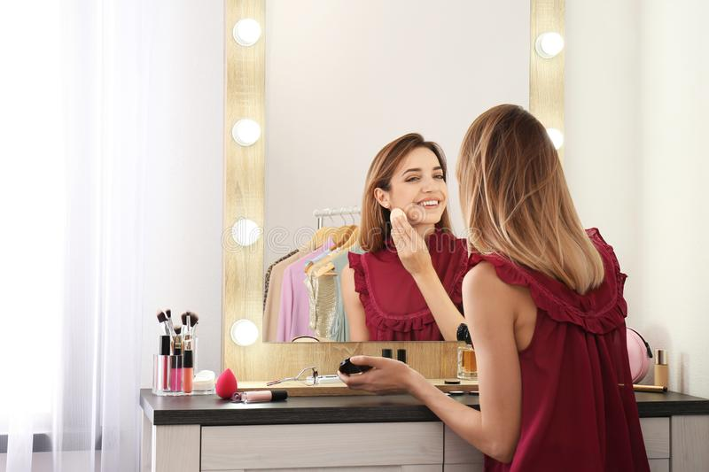 Woman applying makeup near mirror with light bulbs stock photo