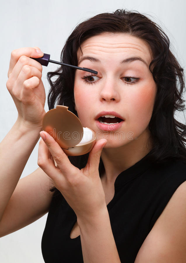 Woman is applying mascara while looking in mirror royalty free stock image