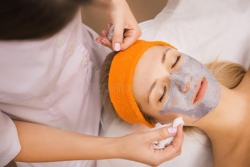 Woman applying mask. Young women applying grey facial mask on her face stock photo