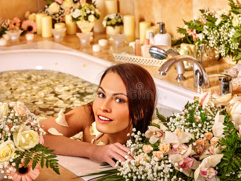 Woman applying moisturizer. Woman applying moisturizer at bathroom with a lot of flowers stock image